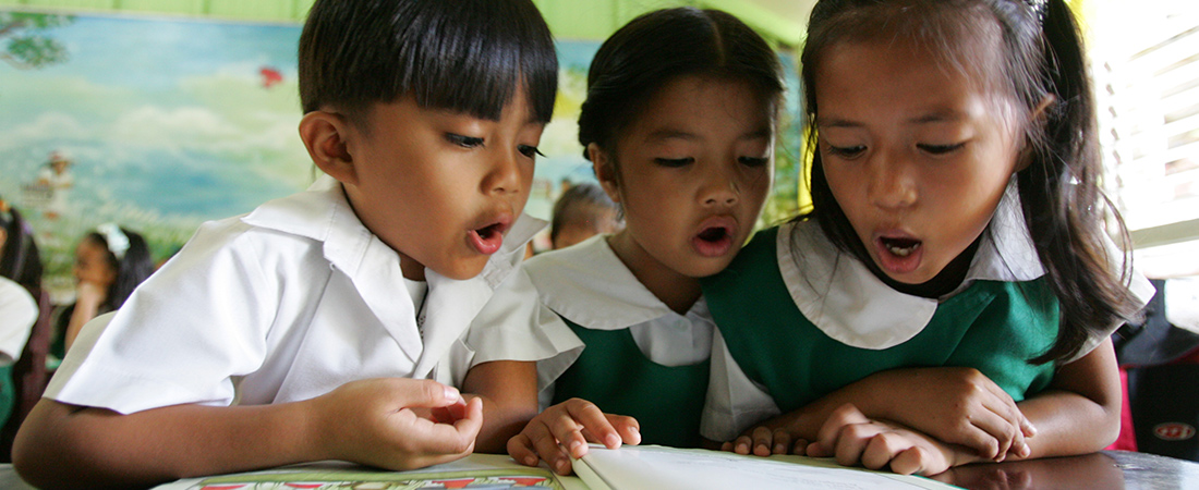 A photo of children reading representing To Improve Literacy, Examine the Book Supply Chain