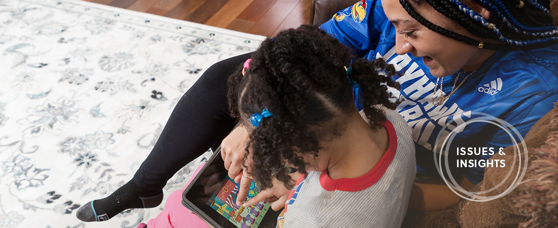 A photo of child and parent using tablet