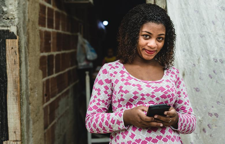 A women using a phone representing What the Tech: Can WhatsApp Support Program Delivery with Busy Families?