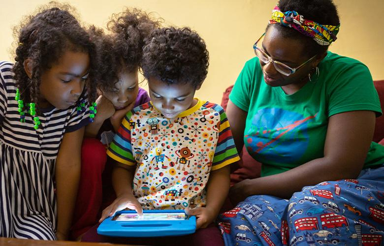A photo of parent and children using tablet