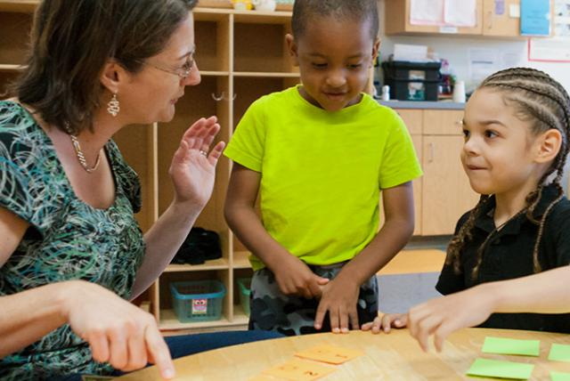 A photo of EDC's Kristen Reed playing a math game with children.