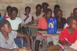 Students in Malawi listening to a radio