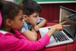 A photo of kids using a computer representing Celebrating Computer Science Education Week