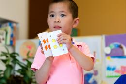 A photo of a young child doing math representing Learning Math with Your Preschoolers: Fun in the Talking and the Playing